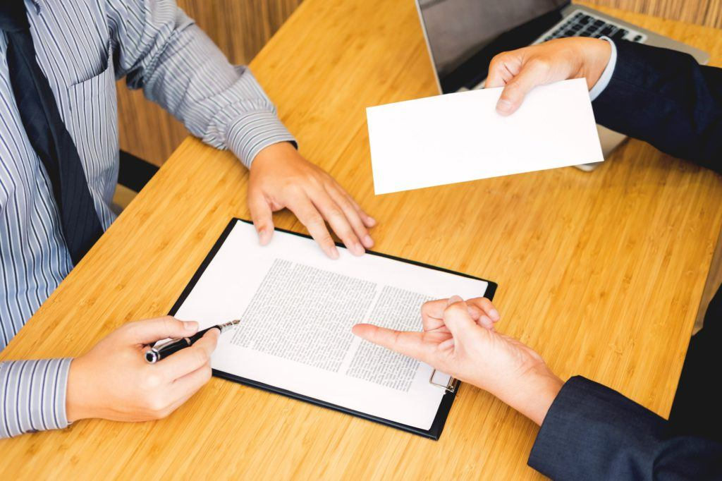 Hand of a businessman hands over a resignation letter final remuneration to executive boss on a