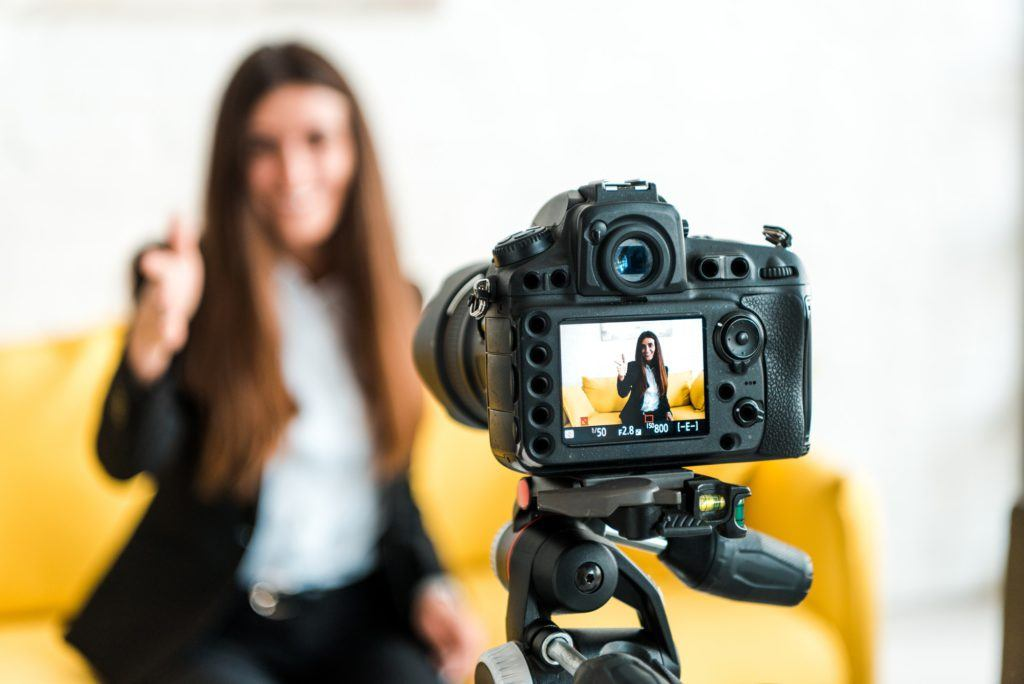 Selective focus of digital camera with happy video blogger showing thumb up on screen