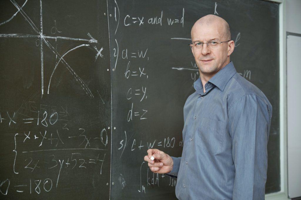 Bald professor in smart casualwear holding piece of chalk while standing by blackboard in classroom