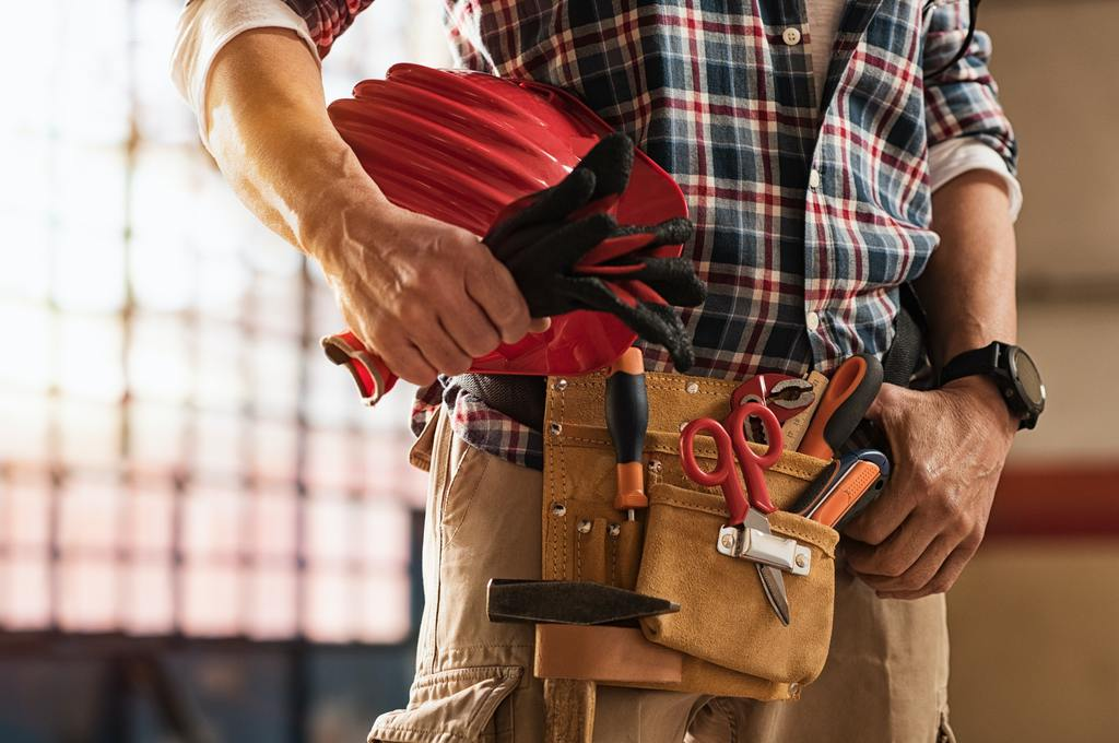 Bricklayer holding construction tools