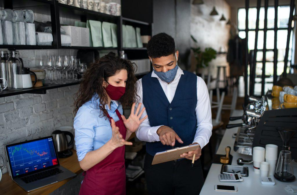 Coffee shop manager discussing issues with waitress in cafe small business and new normal concept