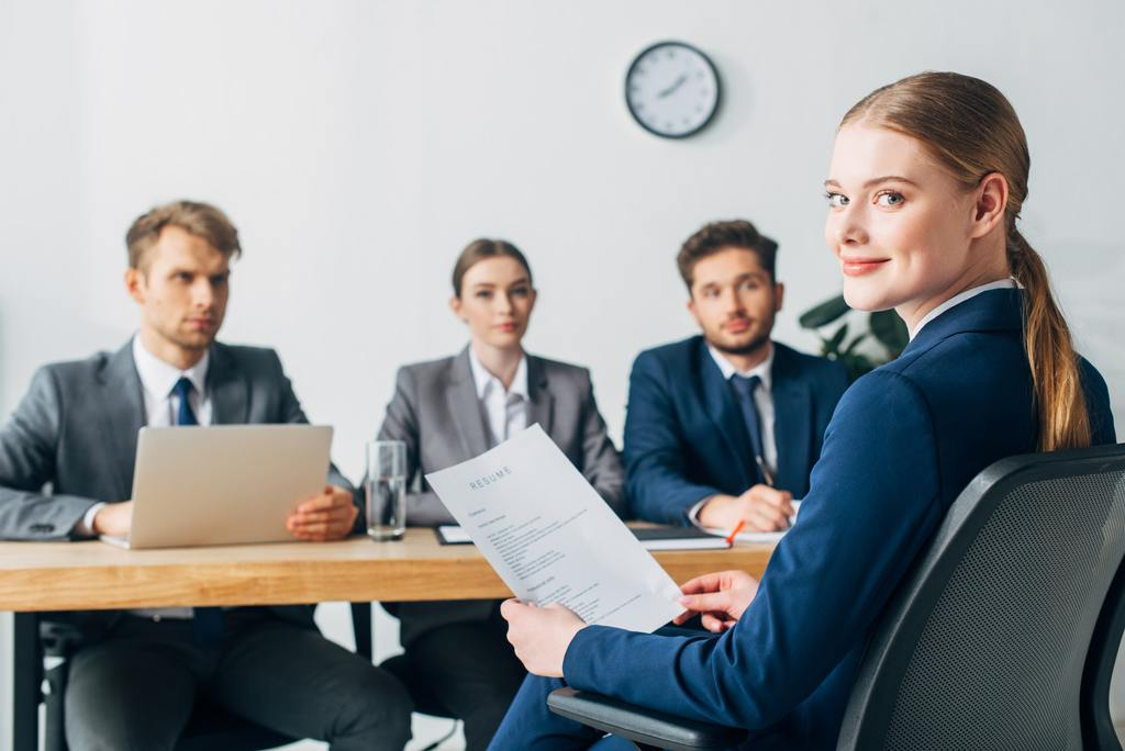 Selective focus of employee looking at camera while holding resume near recruiters