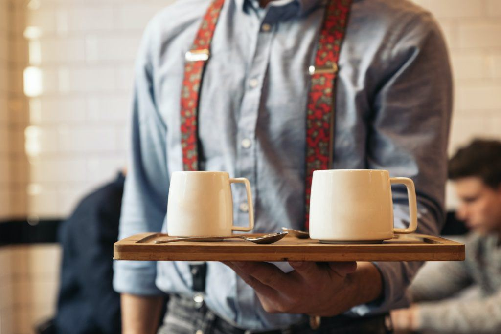 Waiter holding a tray with coffees