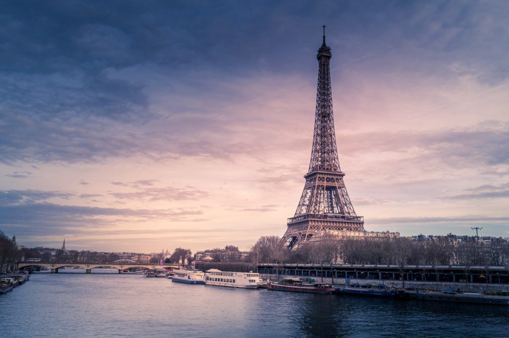 Beautiful wide shot of eiffel tower in paris surrounded by water with ships under the colorful sky