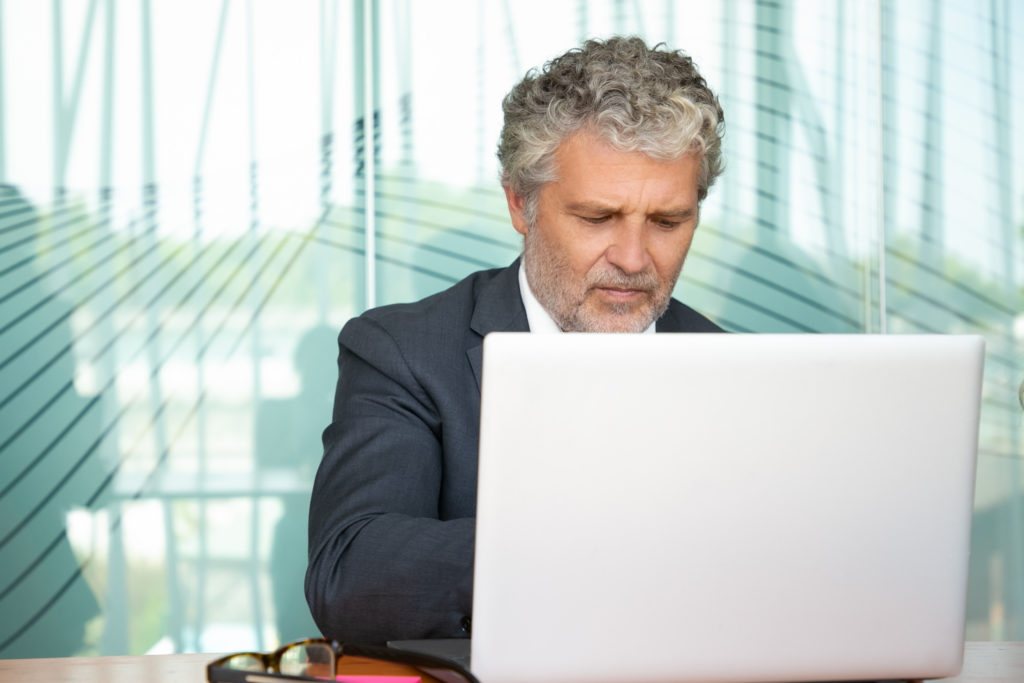 Focused mature executive working at computer in office using white laptop at table m