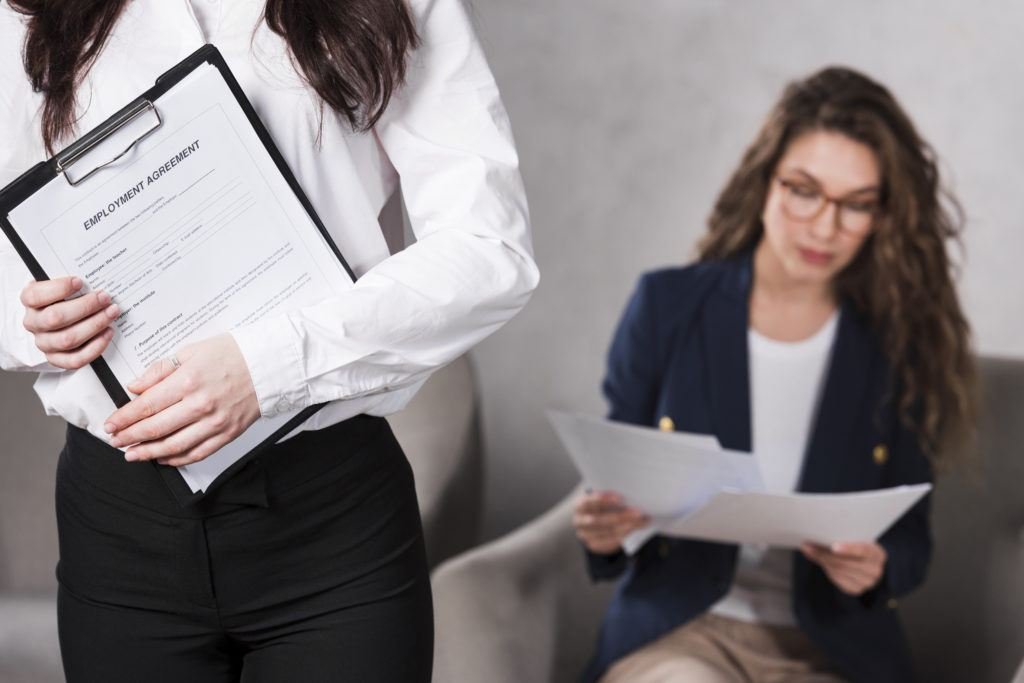 Front view of woman holding contract and another one reading papers