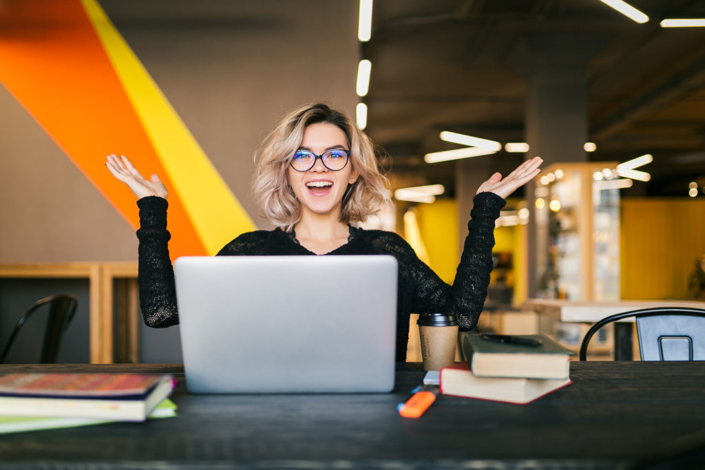 Funny happy excited young pretty woman sitting at table in black shirt working on laptop in co working office wearing glasses