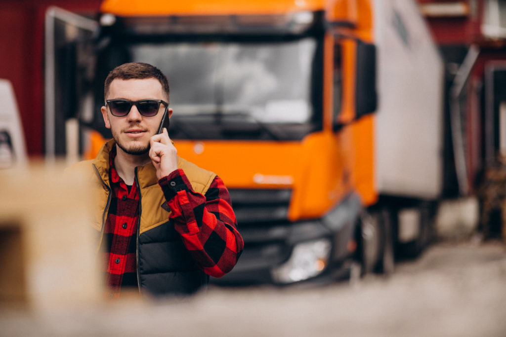 Handsome man truck driver standing by the truck