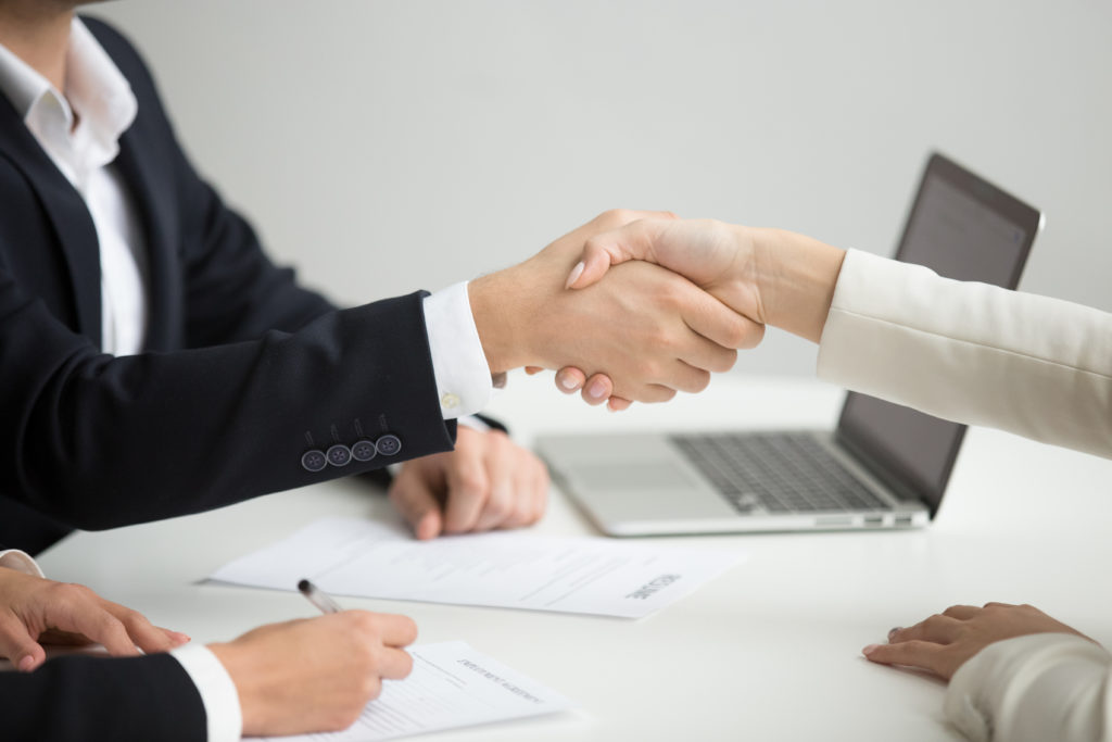 Hr handshaking successful candidate getting hired at new job closeup