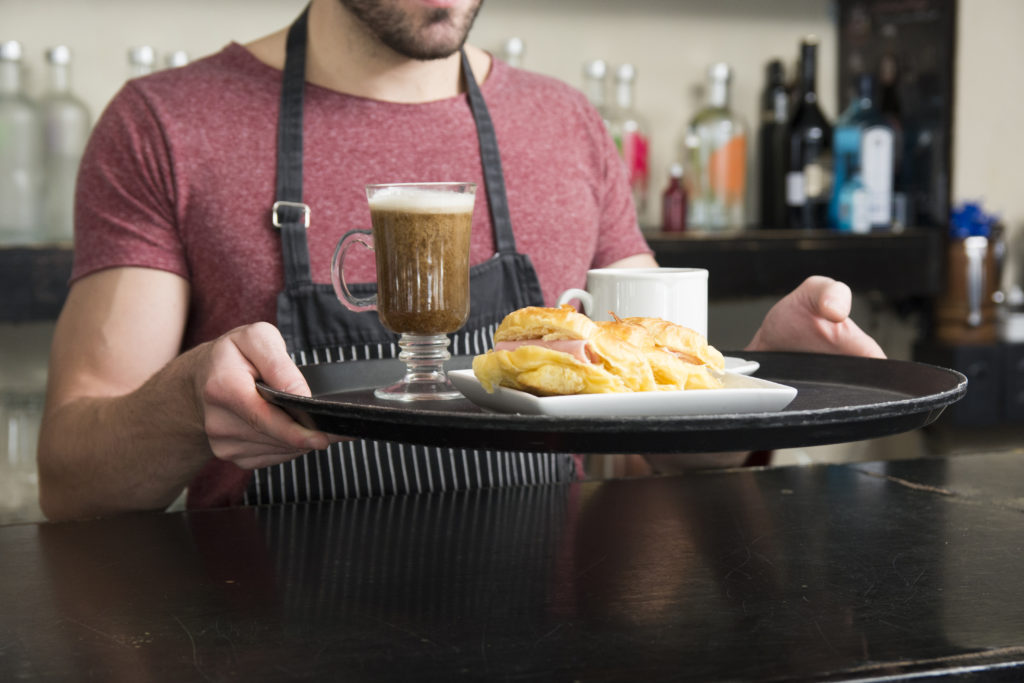 Male waiter holding hamburger and cocktail on tray in the bar