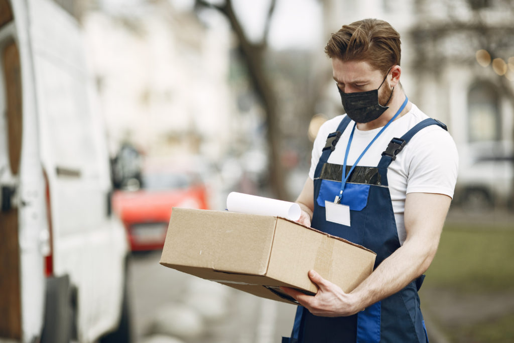 Man by the truck guy in delivery uniform man in medical mask coronavirus concept