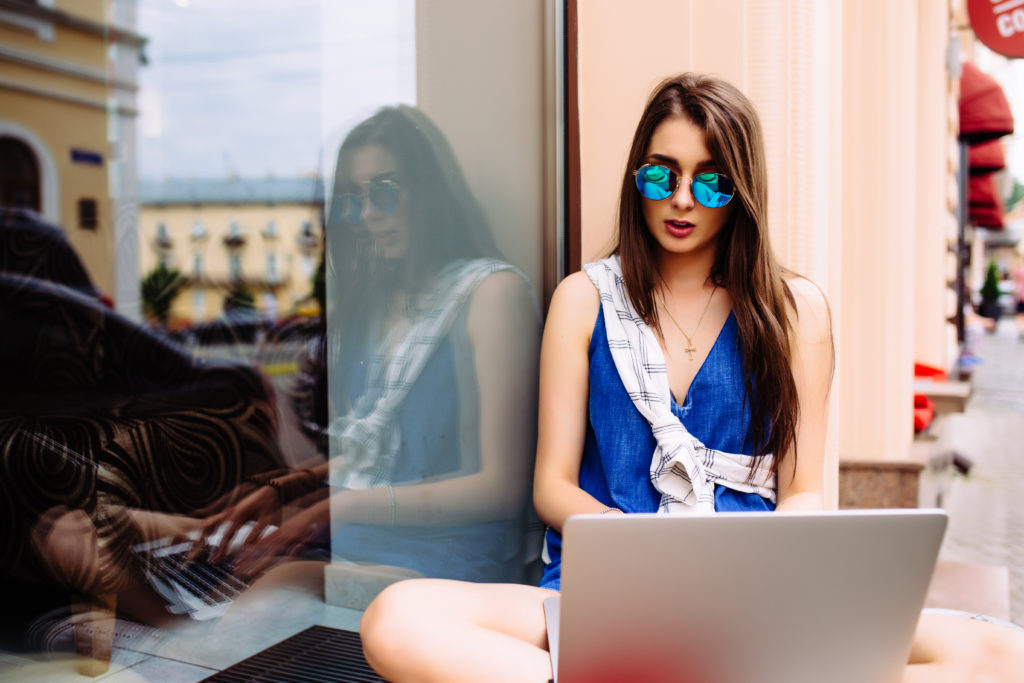 Portrait of pretty young woman sitting during summer day while using laptop and wireless earphone for video call