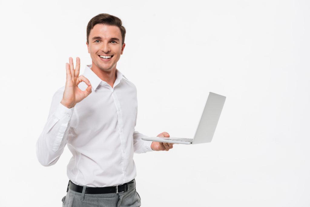 Portrait of smiling handsome man holding laptop